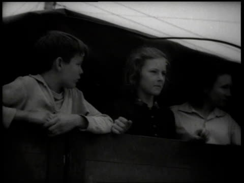 1930s teenagers looking out of back of truck / united states - lavoratore emigrante video stock e b–roll