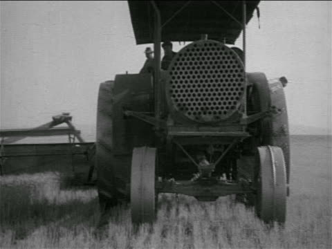 b/w 1930s threshing machine coming towards camera in field / documentary - tractor stock videos & royalty-free footage