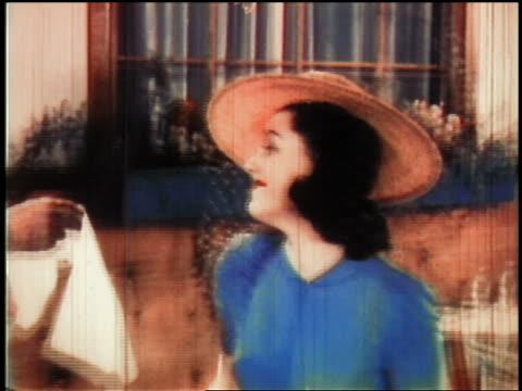 vídeos de stock e filmes b-roll de 1930s ms tilt down woman wearing hat sitting down + smiling at cafe - sentar se