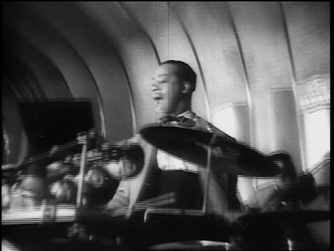 B/W 1930s tilt up Black male jazz drummer with bow tie hitting drumset / Black guitarist in background
