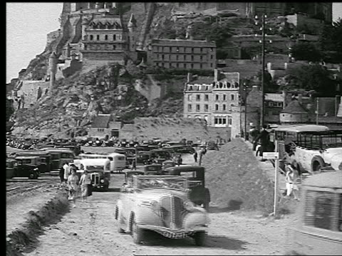 b/w 1930s tilt up from cars in parking lot to mont-st.-michel with houses + church / normandy, france - parcheggio video stock e b–roll
