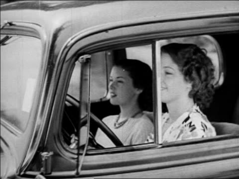 vídeos de stock e filmes b-roll de b/w 1930s tracking shot 2 young women driving with windows down + smiling / industrial - 1930