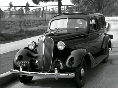 b/w 1930s tracking shot black car (buick?) driving on suburban street - 1930 stock videos and b-roll footage