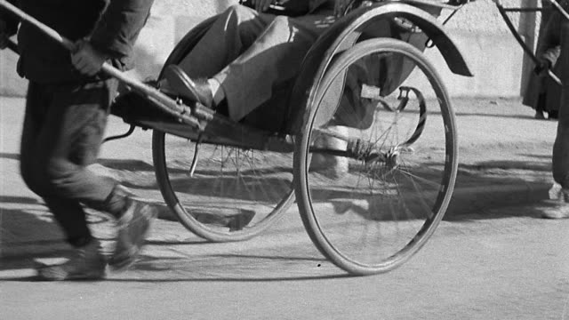 vidéos et rushes de b/w 1930s ms tracking shot line of rickshaws passing on street / asia - pousse pousse