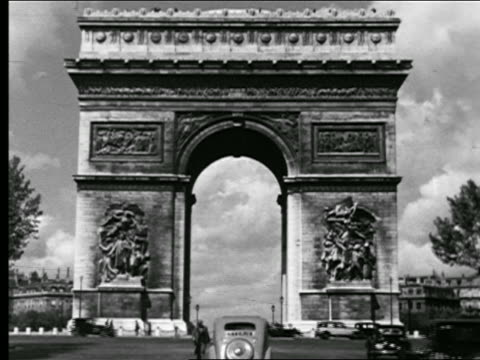B/W 1930s traffic + people walking in front of Arc de Triomphe / Paris, France