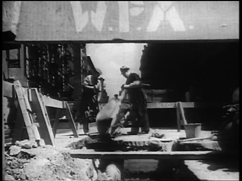 b/w 1930s two men pouring wheelbarrow on road construction site in city during great depression - new deal video stock e b–roll