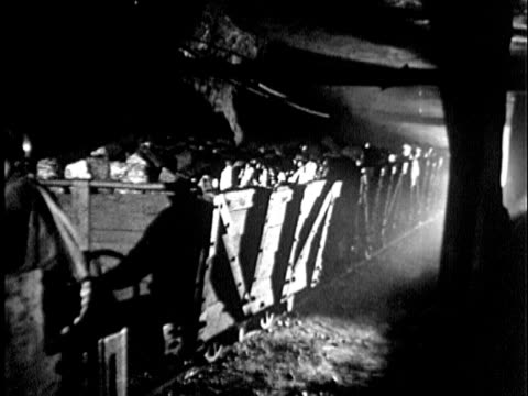 b/w montage 1930s two miners driving mine cars through coal mine, maryland / usa - coal mine stock videos and b-roll footage