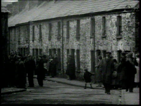 uk great depression ws people standing outside in poor neighborhood connected homes ms extended family by entrance to stone structure house barn two... - great depression stock videos & royalty-free footage