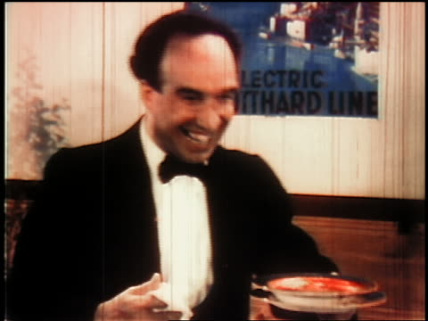 1930s MS waiter nodding + laughing with bowl in hand