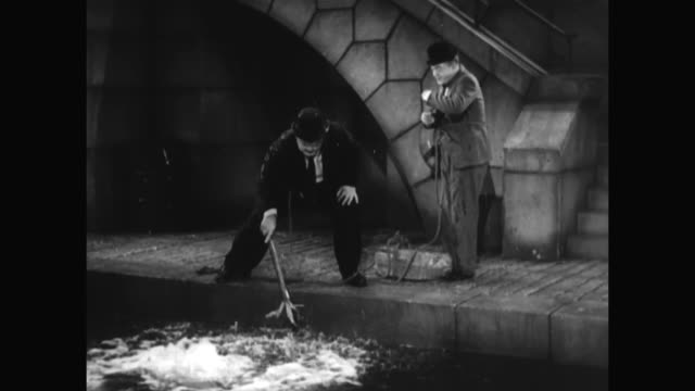 1930s when laurel and hardy test the depth of the water with an oar, it is destroyed by a fish - 1930 1939 stock-videos und b-roll-filmmaterial