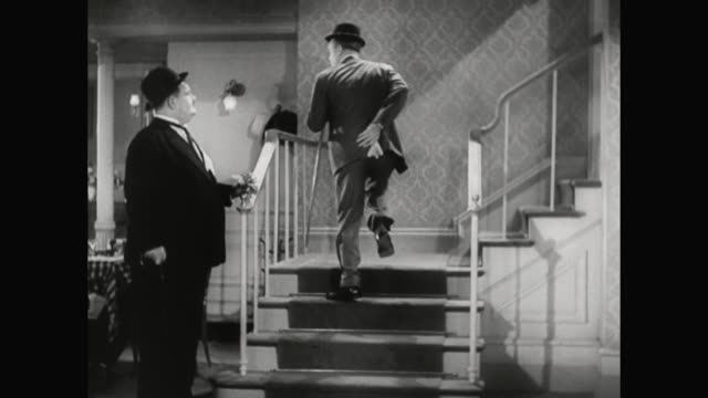 1930s when laurel misses the staircase, hardy gives him a smack - 1930 1939 stock-videos und b-roll-filmmaterial