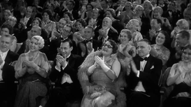 vídeos de stock e filmes b-roll de 1930s wide shot elegantly dressed audience sitting in theater, smiling and clapping for performance - 1930
