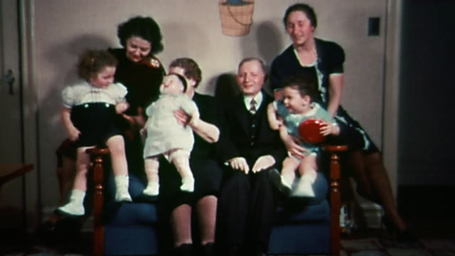 1930s wide shot grandparents posing on sofa with 2 women, 2 small children and baby doll