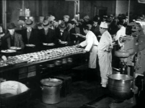 1930s wide shot line of men being served food in soup kitchen / great depression - soup kitchen stock videos & royalty-free footage