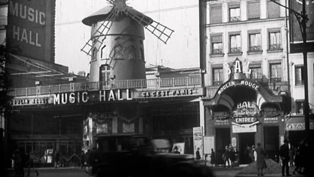 stockvideo's en b-roll-footage met 1930s wide shot moulin rouge nightclub with windmill spinning, streetcars and traffic in foreground / paris - 1930