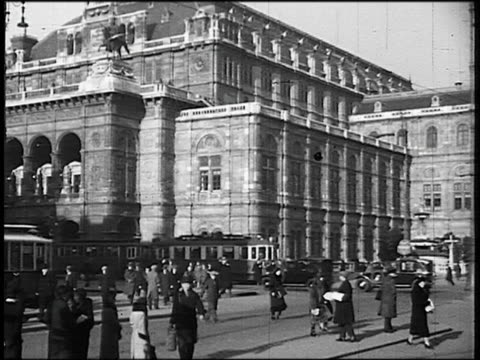 B/W 1930s wide shot PAN Vienna State Opera House (Wiener Staatsoper) with trolley, traffic + crowds in front / Austria