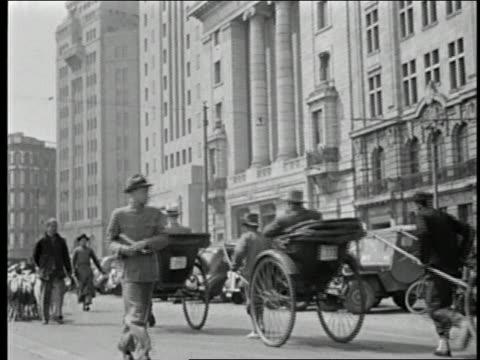 vidéos et rushes de 1930s wide shot western businessmen riding in rickshaws / buildings in background / men herding goats in foreground - pousse pousse