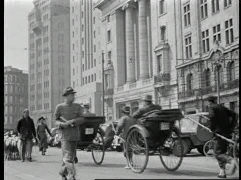 1930s wide shot western businessmen riding in rickshaws / buildings in background / men herding goats in foreground - hjord bildbanksvideor och videomaterial från bakom kulisserna