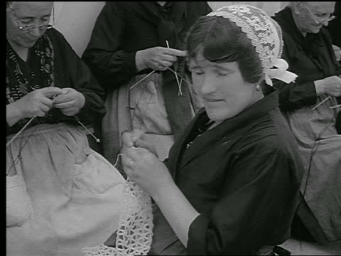 B/W 1930s woman in traditional lace bonnet crocheting lace / other women in background / Brittany, France