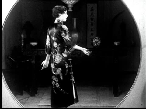 vidéos et rushes de 1930s ms woman modeling kimono/ ws models stepping through round partition as man bows at them/ san francisco, california - homme dans un groupe de femmes