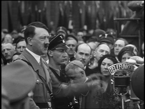 vídeos de stock, filmes e b-roll de 1930s/40s adolf hitler surrounded by crowd giving speech into microphone outdoors - adolf hitler
