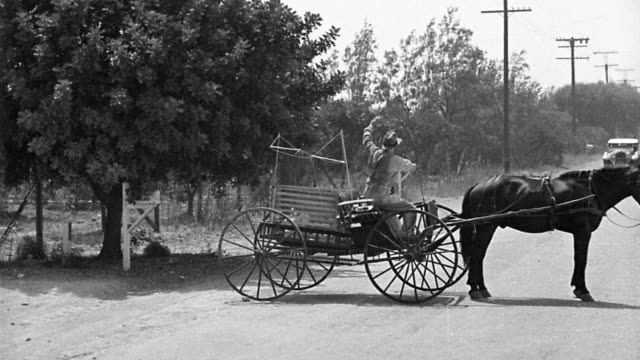 vidéos et rushes de b/w 1930s/40s car crashing through horse-drawn wagon stopped on dirt road - accident domestique