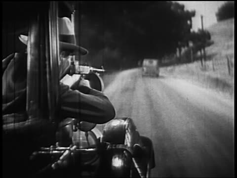 B/W 1930s/40s car point of view from behind man shooting Tommy gun out window of moving car (rear projection)