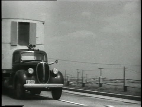 b/w 1930s/40s close up pan ford tractor trailer passes camera on country highway - ford truck stock videos and b-roll footage