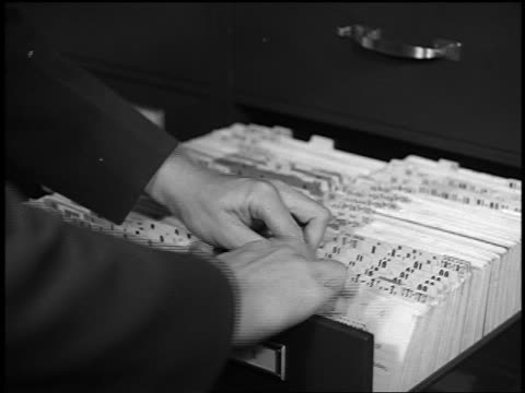 b/w 1930s/40s close up man's hands pulling fingerprint file from drawer in police station - filing cabinet stock videos & royalty-free footage