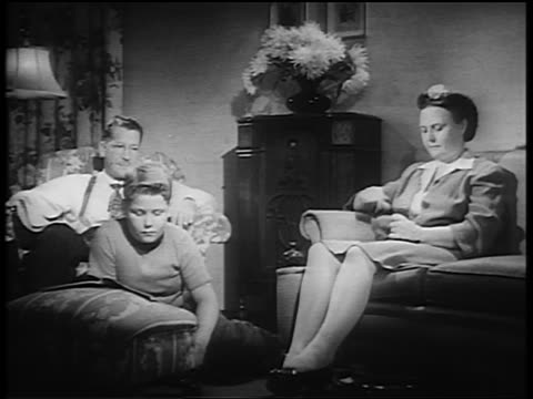 stockvideo's en b-roll-footage met b/w 1930s/40s couple + boy sitting in living room listening to radio / man reaches to turn knob - 1930