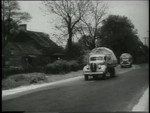 B/W 1930s/40s Ford trucks with cargo drive toward camera on country road / small house next to road