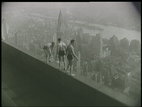 B/W 1930s/40s high angle 3 male acrobats doing stunt on ledge of 86th floor of Empire State Building / NYC