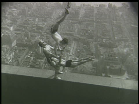 b/w 1930s/40s high angle 3 male acrobats doing stunt on ledge of 86th floor of empire state building / nyc - akrobat stock-videos und b-roll-filmmaterial