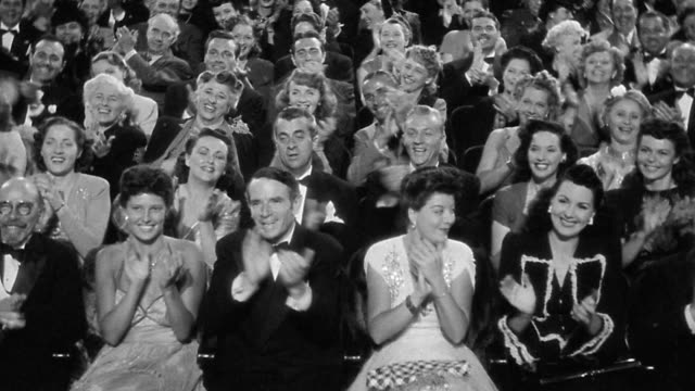 B/W 1930s/40s high angle audience watching + reacting with laughs + applause