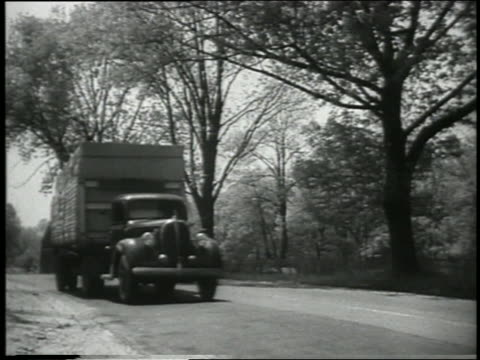 b/w 1930s/40s low angle ford tractor trailer passes camera on country road - ford truck stock videos and b-roll footage
