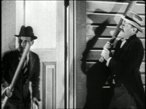 b/w 1930s/40s man exiting house with baseball bat / man hiding in background hits him on head / feature - baseball bat stock videos & royalty-free footage