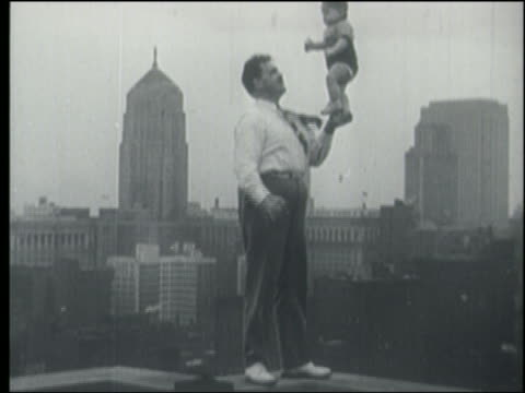 B/W 1930s/40s man on rooftop balancing baby by its feet on his hand / city skyline in background