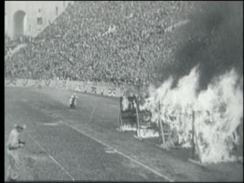 vídeos y material grabado en eventos de stock de b/w 1930s/40s motorcyclist riding thru multiple walls of fire in crowded stadium - stunt