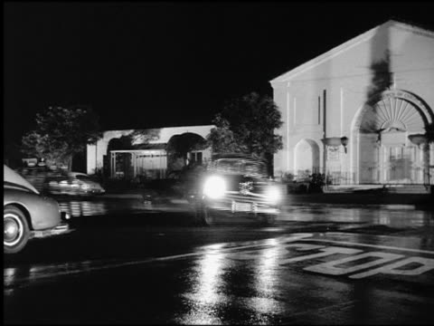 b/w pan 1930s/40s police car chasing car around curve + down suburban street at night - chasing stock videos and b-roll footage