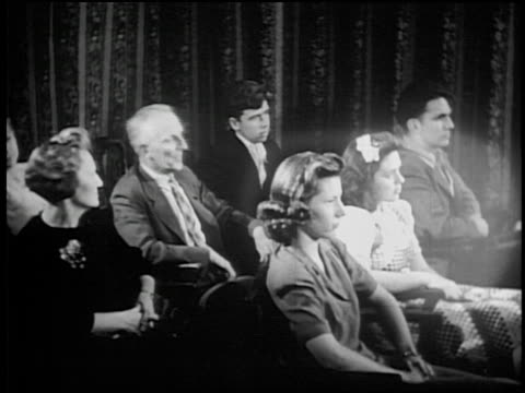 b/w 1930s/40s senior man sitting in audience sneezes leaving halo around girl in front of him - sneezing stock videos & royalty-free footage