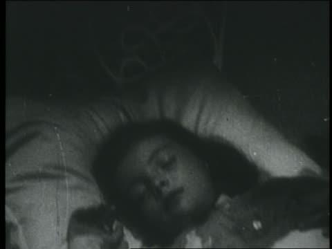 b/w 1930s/40s tilt up from little girl sleeping to jolly santa claus speaking - jolly video stock e b–roll