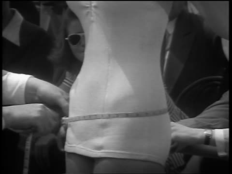 b/w 1940/50s close up tilt up man's hands uses measuring tape around woman's waist + breasts / swimsuit contest - measuring stock videos & royalty-free footage