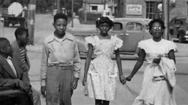 1940s - 1950s black and white wide shot teenage boy and two teenage girls holding hands walking on sidewalk / tulsa, ok - african american ethnicity stock videos & royalty-free footage