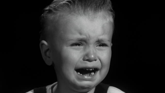 1940s / 1950s close up face of young boy crying against black background