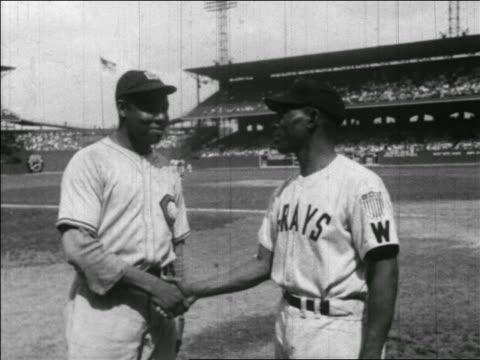 vídeos y material grabado en eventos de stock de b/w 1940s 2 black baseball players in negro league shaking hands on field - uniforme de béisbol