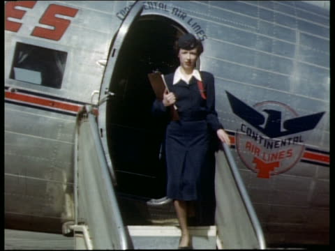 1940s / 50s female flight attendant exiting Continental airplane outdoors