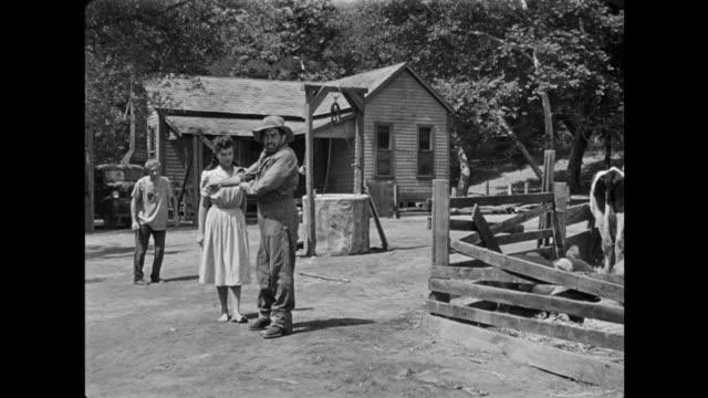 1940s a stone faced farmer instructs man to get his gun for him - ヒルビリー点の映像素材/bロール