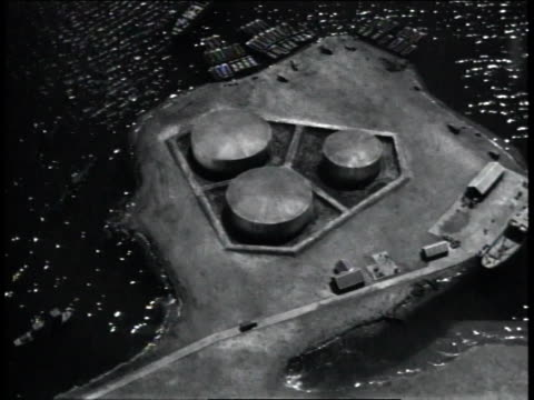 stockvideo's en b-roll-footage met 1940s aerial oil storage tanks surrounded by water on a peninsula of land / united states  - kleine groep dingen