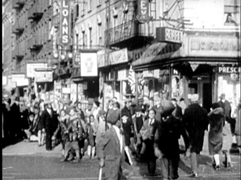 B/W WS 1940s African-American boys walking on street in Harlem towards camera / New York City, New York