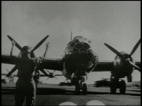 male ground crew waving in b-29 superfortress taxiing toward frame on runway, various crew loading large bomb, into bomb bay of bomber aircraft.... - b29 stock videos & royalty-free footage